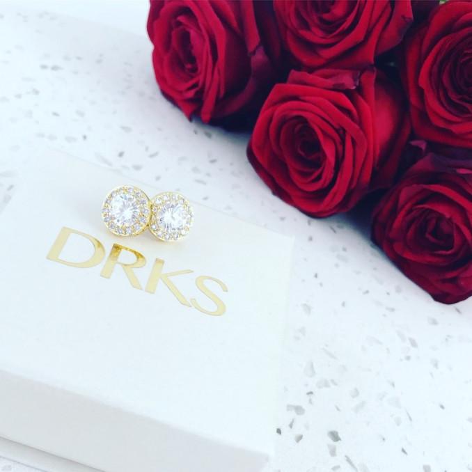 Gouden oorknopjes op marmer met roosje voor valentijn