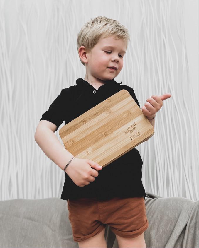 Jongetje houdt serveerplank vast