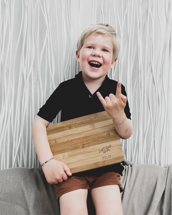 Serveerplank van hout in handen van jongetje
