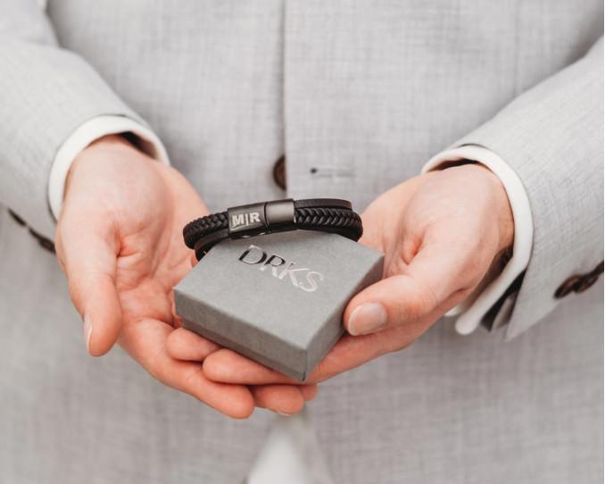Man draagt mooie zwarte leren armband met gravering