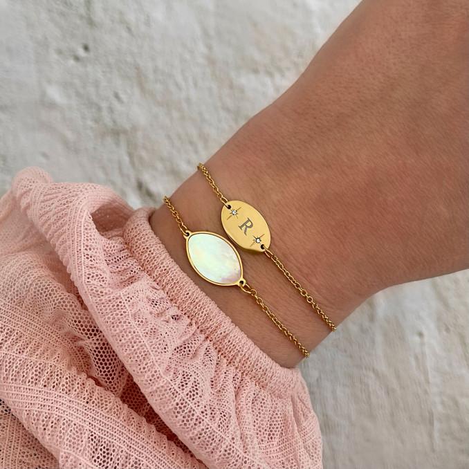 vrouw draagt gouden mix van armbanden om pols