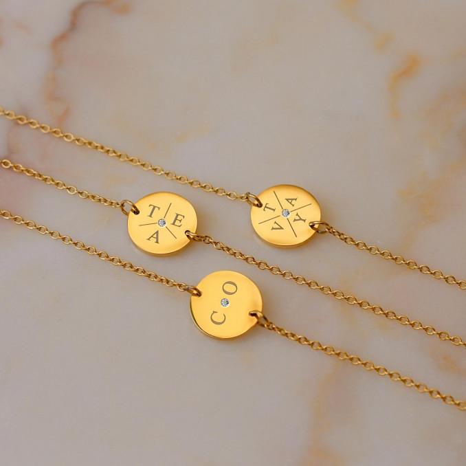 Gouden initial armbanden met steentje op marmer plaatje
