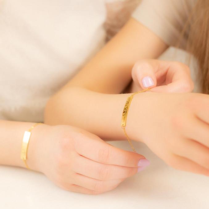 Moeder en dochter dragen gouden matching armbandjes