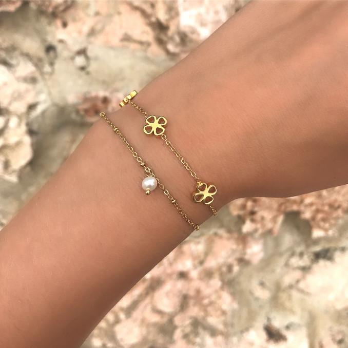 Mooie gouden armbanden om de pols met een klavertjes