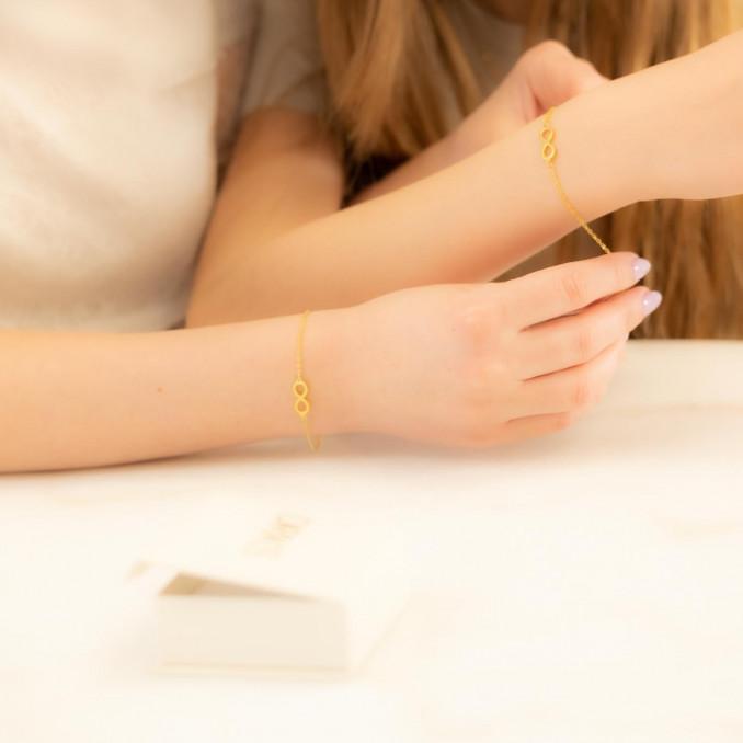 Moeder en dochter dragen gouden infinity armbandjes