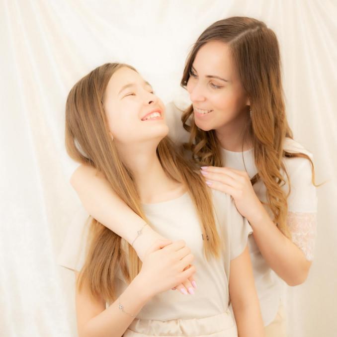 Moeder en dochter dragen zilveren armbandjes met klavertje