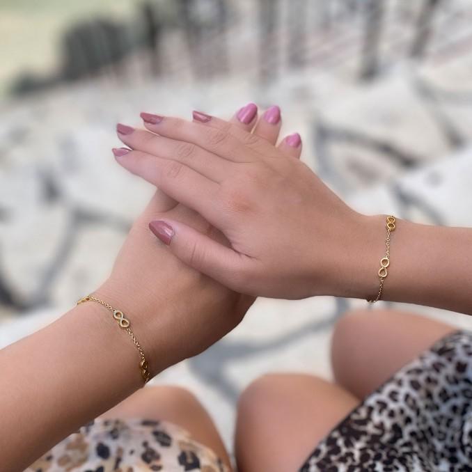 Moeder en dochter dragen samen een sieraad in het goud met infinity teken