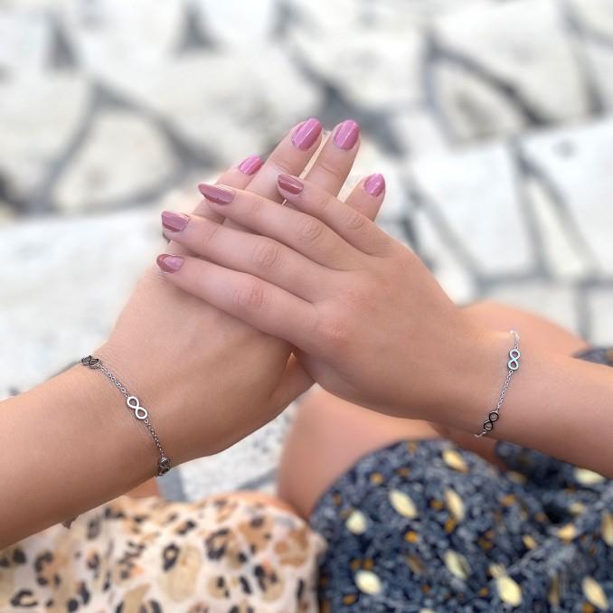 Moeder en dochter dragen zilveren armbandjes met infinity tekens