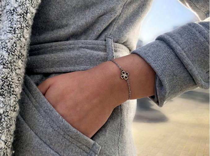 Vrouw met grijze kleding en zilveren clover armbandje