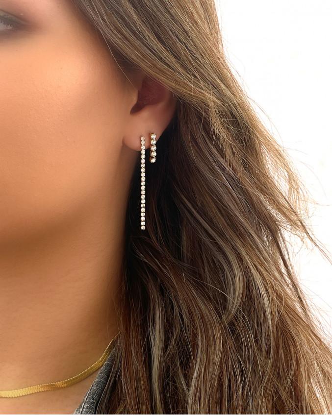Vrouw draagt zilveren earparty met tennis earrings
