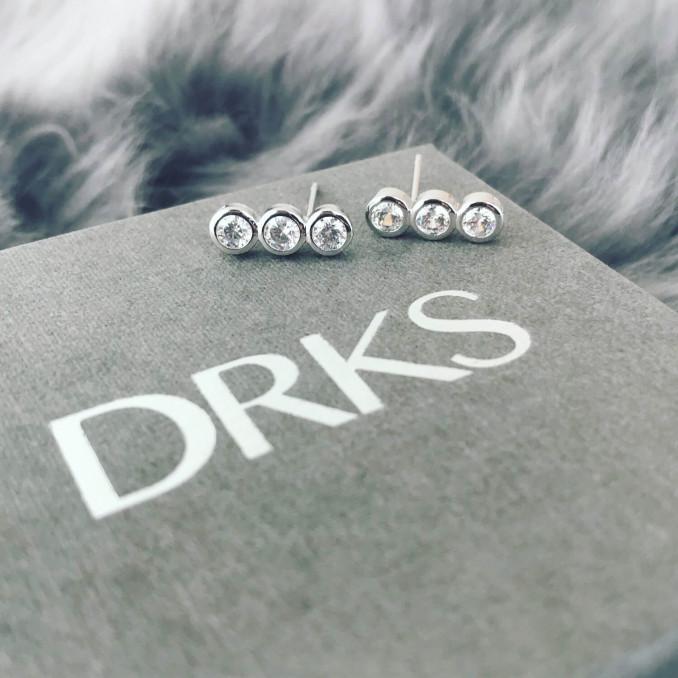 Zilveren oorbellen met steentjes op sieradendoosje DRKS