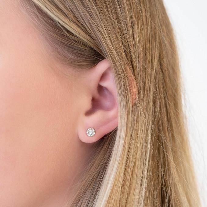 Vrouw draagt gouden oorknopjes in het oor voor een simpele look