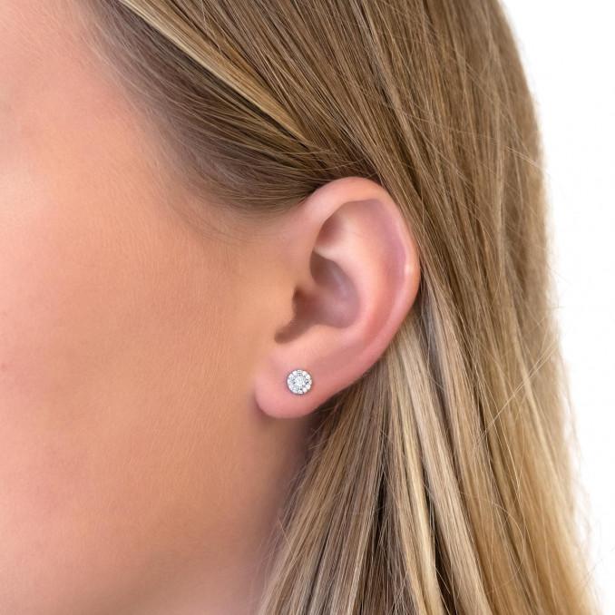Vrouw draagt zilveren oorknopjes in het oor voor een simpele look