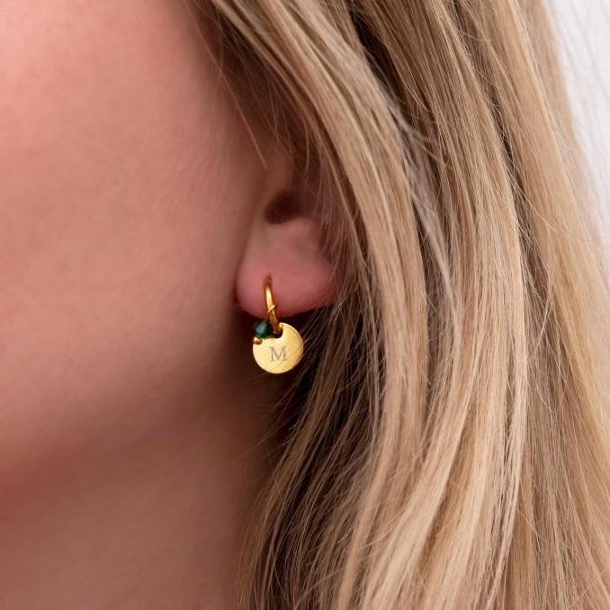 Vrouw draagt birthstone oorbellen in oor