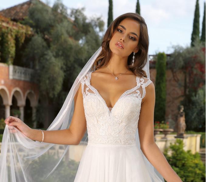 De bruid draagt de lange druppelvormige oorbellen