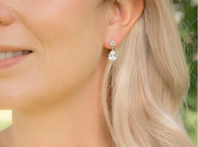 vrouw met hangende zilveren oorbellen met kristallen van drks