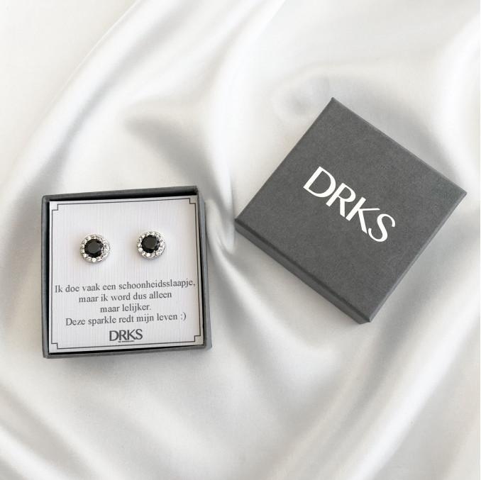 Zwarte oorbellen met een sparkle in een sieradendoosje