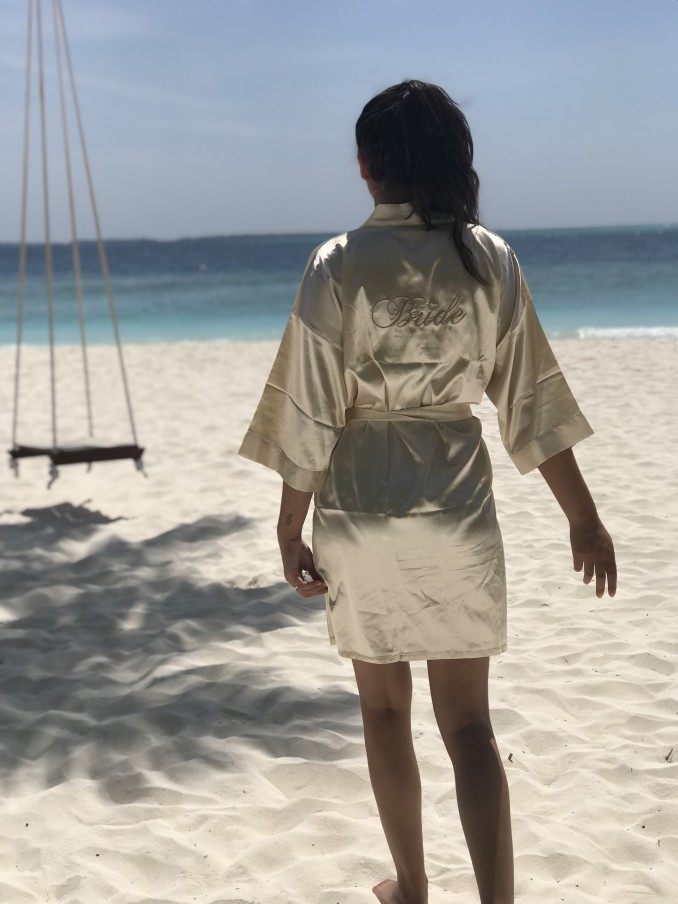 Vrouw op strand met de champagne kimono