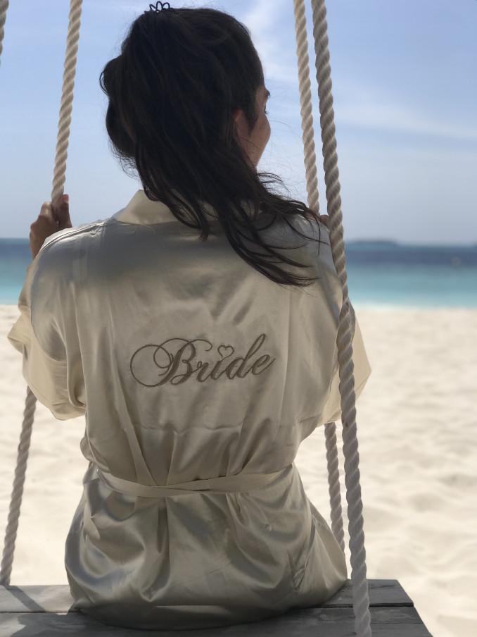 Vrouw op het strand met de champagne kimono in een schommel