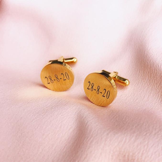 Gouden graveerbare manchetknopen op een roze kleedje