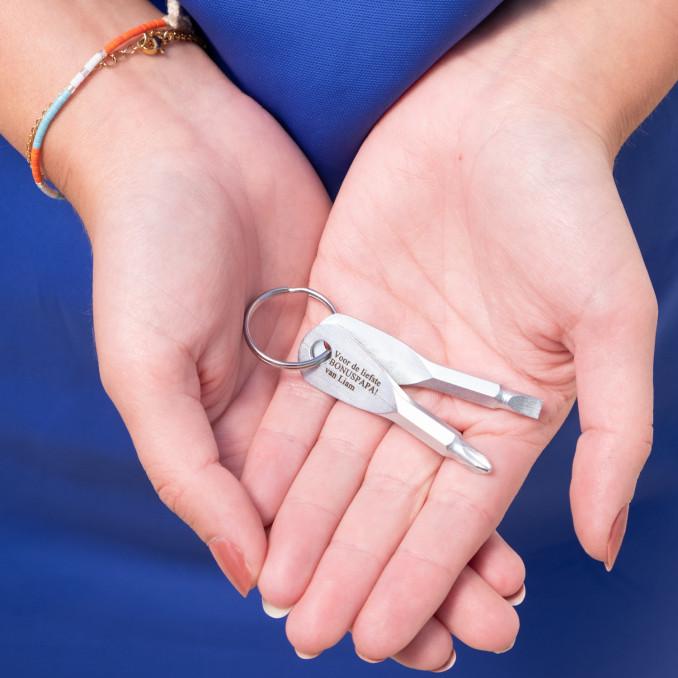 Vrouw houd sleutelhanger vast met gravering