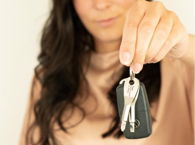Vrouw geeft sleutel hanger met naam cadeau