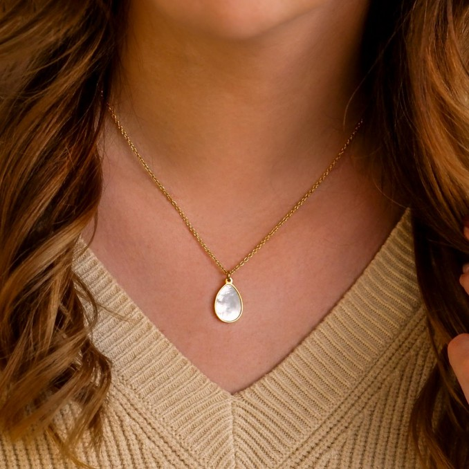 Vrouw draagt gouden sea shell ketting in druppelvorm