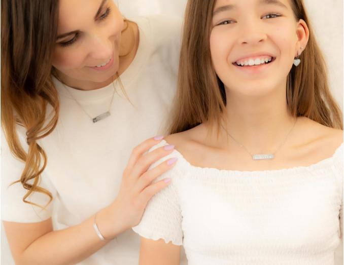 Moeder en dochter dragen matching zilveren kettingen