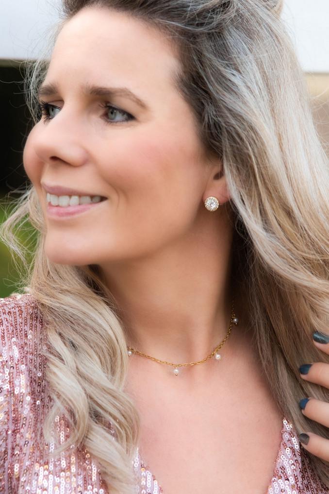 Vrouw draagt gouden oorbellen samen met mooie parel kettingen