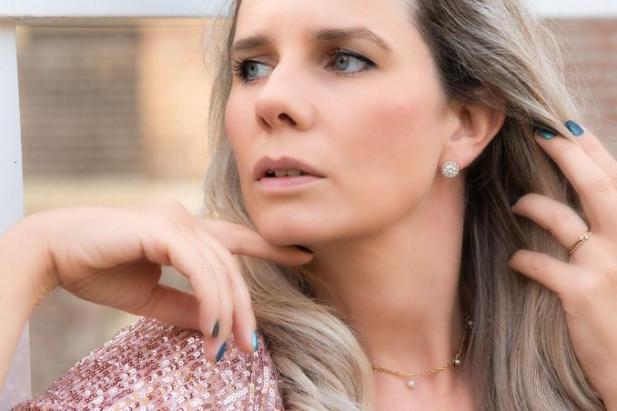 Vrouw draagt mooie oorbellen in een sieradendoosje met een mooie sparkle