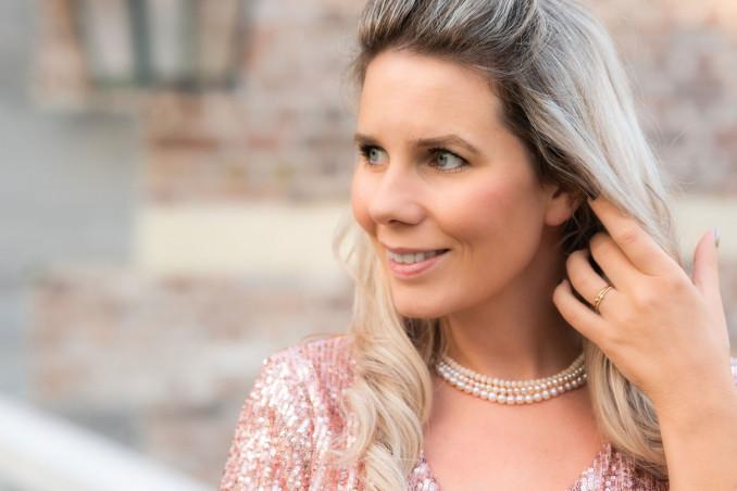 Vrouw draagt parelketting met nude kleurige parels om de hals