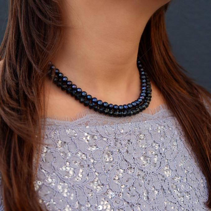 Mooie parelketting om de hals in een donkerblauwe kleur
