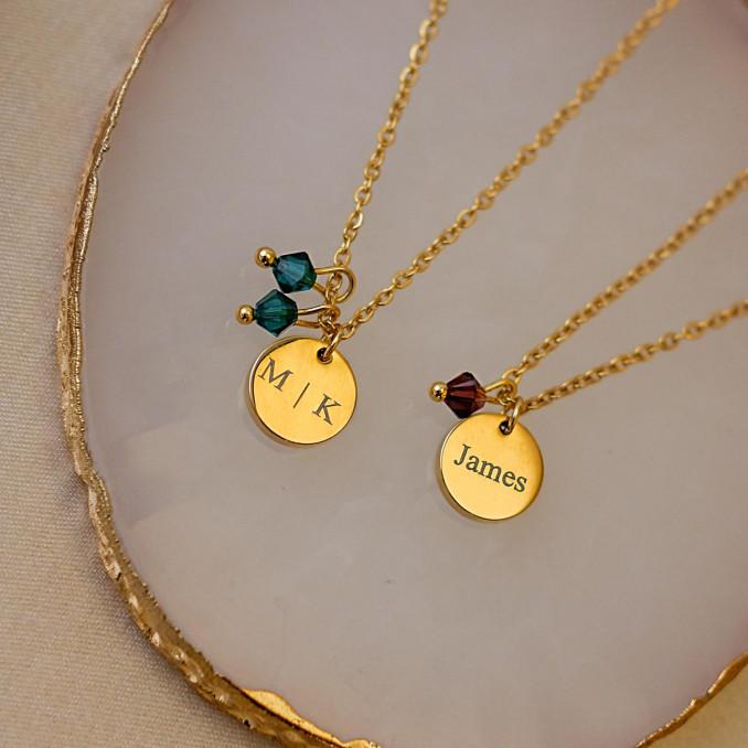 Twee birthstone kettingen op marmer in de kleur goud