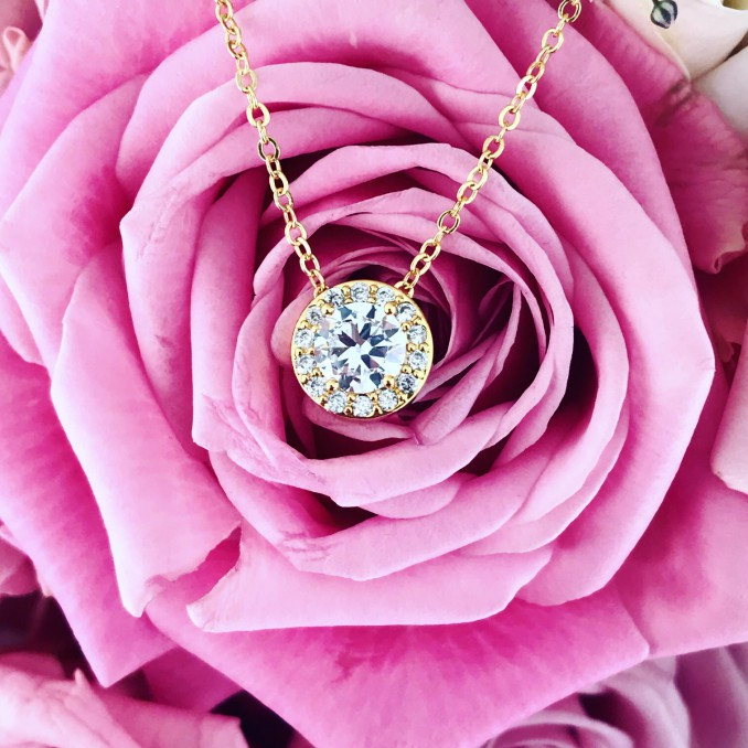 Gouden ketting met ronde hanger samen met roos
