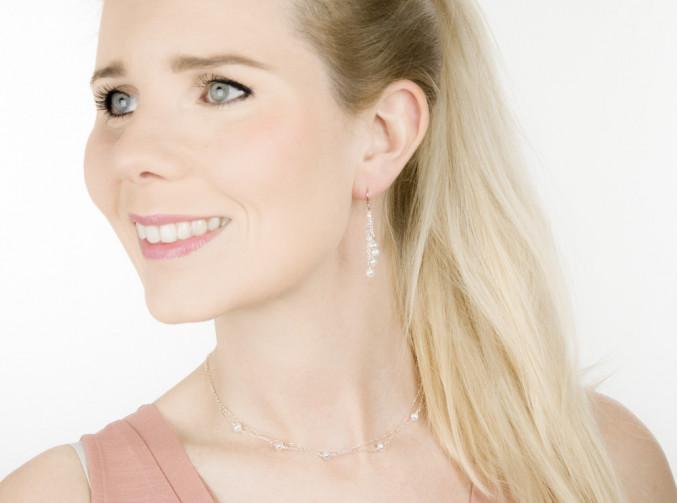 Blonde vrouw draagt sieraden voor de bruid met mooie zoet water parels
