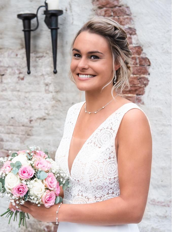 Vrouw draagt mooie set van parel sieraden om de hals en in het oor