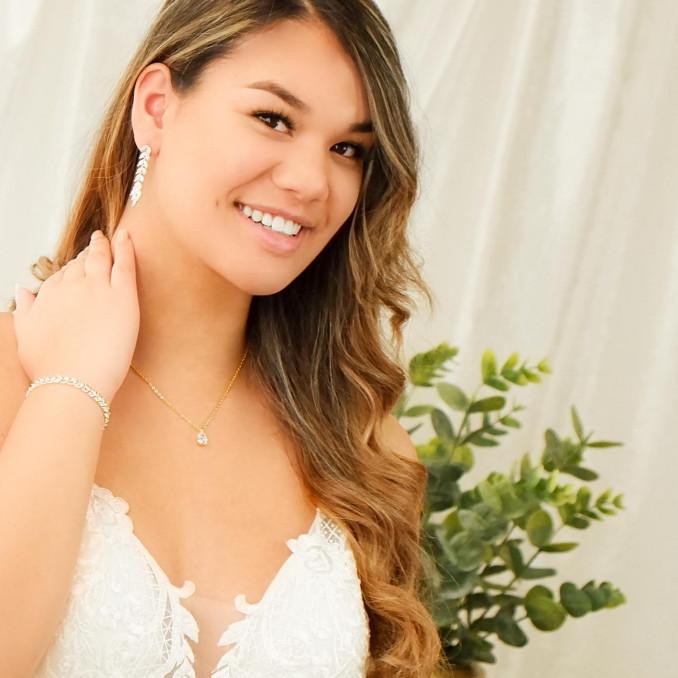 Mooie bruid met een sieradenset in de kleur goud om te kopen