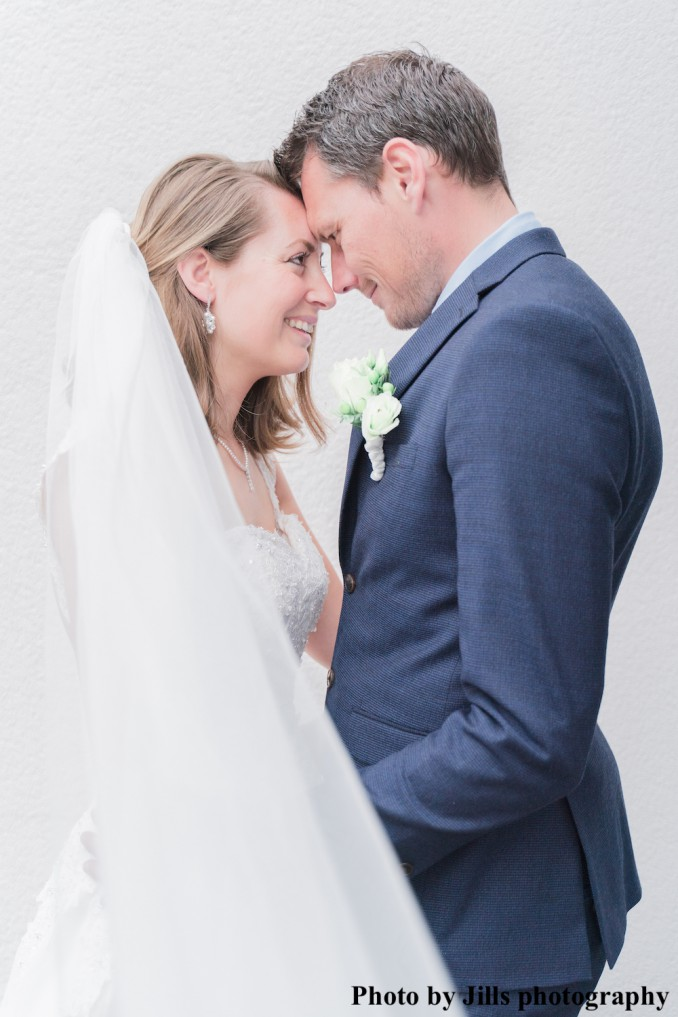 Bruid draagt parel oorbellen en parel kettingen