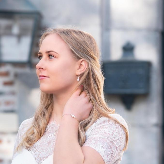 Vrouw draagt een mooie look van parelsieraden in het goud