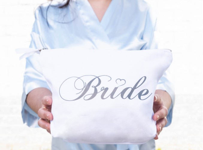 Vrouw houd toilettas in het wit vast voor bruid