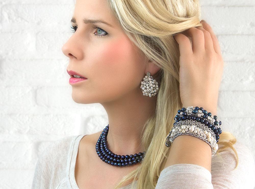 Vrouw draagt mooie parelsieraden om de hals en om de pols