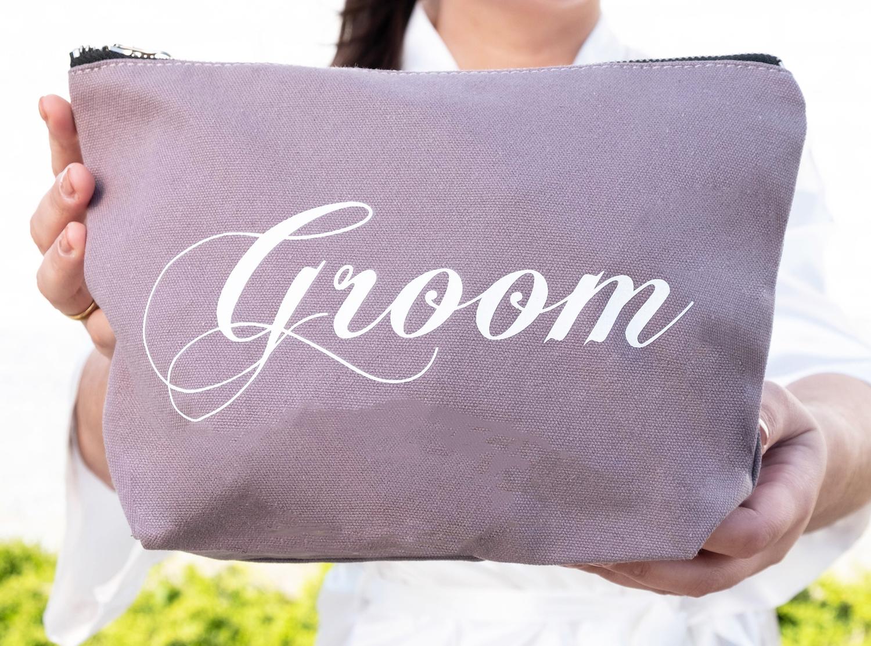 bruid houdt groom toilettas voor de bruidegom vast