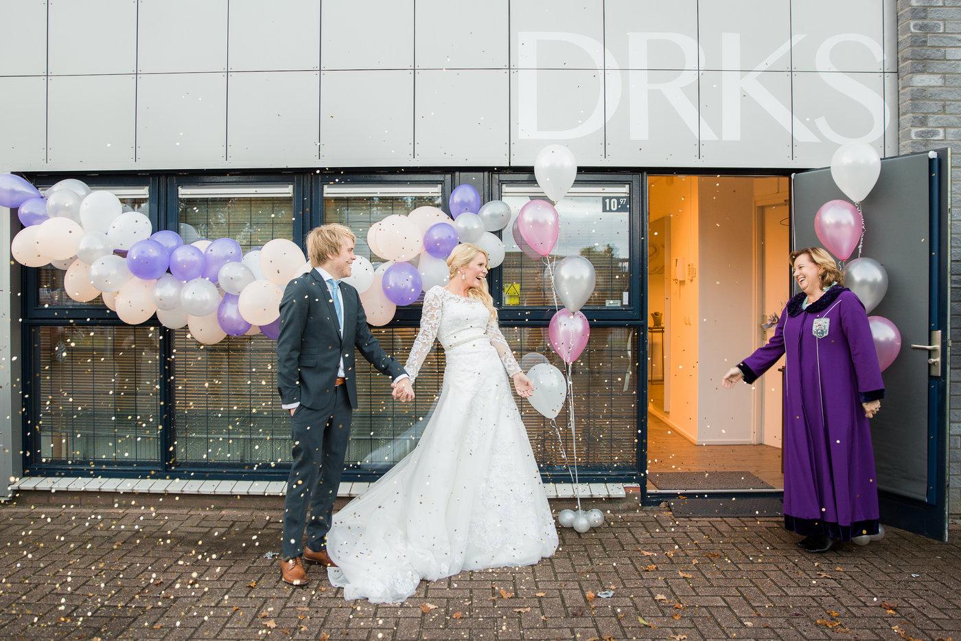 vrolijk bruidspaar met confetti
