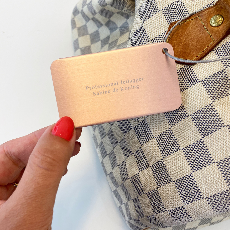 Rose gouden kofferlabel aan lichte tas
