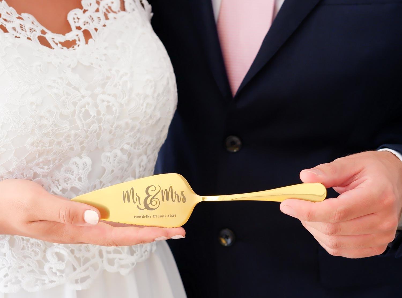 Goudkleurige taartschep voor het bruidspaar