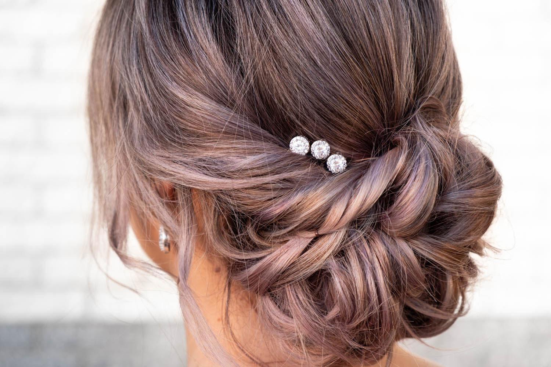 Vrouw draagt drie haarpinnetjes met blonde haren