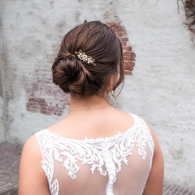 Vrouw draagt een goudkleurige haarspeld voor een bruidslook
