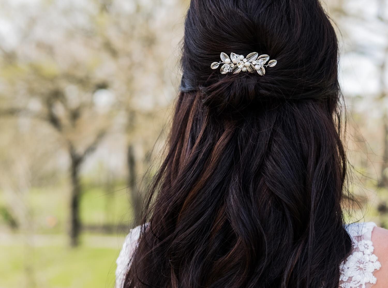 bruid met zilveren haaraccesoire van drks met parels en blaadjes