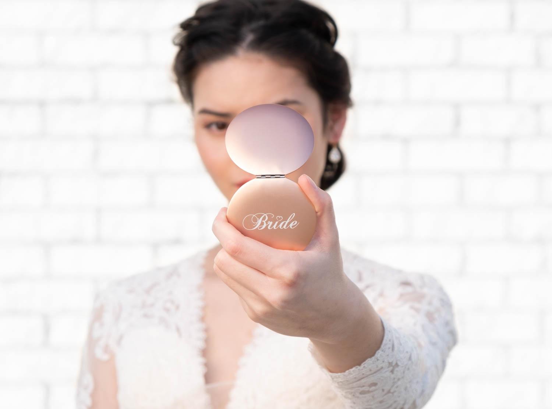 Bruid met rose kleurig spiegeltje voor de bruid