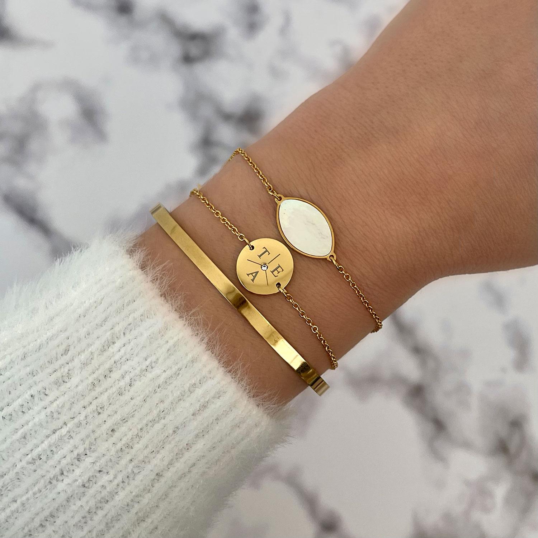 Gouden sea shell armband gecombineerd met initial armband en bangle